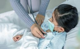 Doctor heal patien asian kid on hospital bed. Medicine virus situation when kid have high fever. Doctor use stethoscope to hear pulp stock image