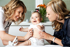 Woman Doctor with Mother and Baby Stock Photo