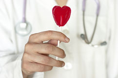 Doctor. Heart shaped lollipop. Stethoscope Stock Photography