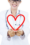 Doctor with heart symbol. Friendly doctor showing a heart symbol. isolated on white stock image