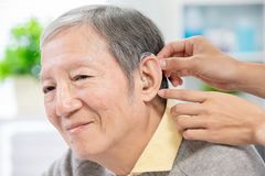 Doctor help patient wear audiphone. Doctor help elder patient wear audiphone to improve his hearing stock photography