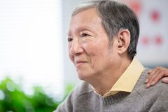 Doctor help patient wear audiphone. Doctor help elder patient wear audiphone to improve his hearing stock photo