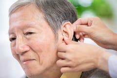 Doctor help patient wear audiphone. Doctor help elder patient wear audiphone to improve his hearing stock image