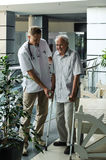 Doctor helping elderly man to walk on crutches Stock Images