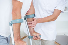 Doctor helping her patient walking with crutch Royalty Free Stock Images