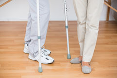 Doctor helping her patient walking with crutch Stock Image