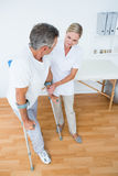 Doctor helping her patient walking with crutch Stock Photography