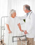 Doctor helping his patient to walk Stock Photos