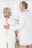 Doctor helping his patient to walk Stock Image