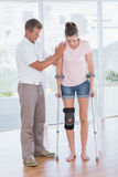 Doctor helping his patient walking with crutch Stock Images