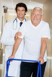 Doctor Helping An Old Man With His Walker Royalty Free Stock Image