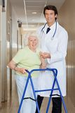 Doctor Helping An Old Woman With Her Walker Royalty Free Stock Photos
