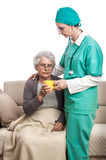 Doctor helping old woman at home Stock Image