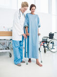 Doctor helping patient in crutches at the hospital. Full length of a doctor helping patient in crutches at the hospital Royalty Free Stock Photos