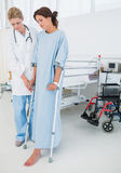 Doctor helping patient in crutches at hospital. Full length of a doctor helping patient in crutches at the hospital Stock Photo