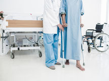 Doctor helping patient in crutches at the hospital. Low section of a doctor helping patient in crutches at the hospital Royalty Free Stock Photos