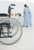 Doctor helping patient to walk with wheelchair in foreground Stock Photo
