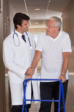 Doctor helping Patient use Walker. A doctor assisting a senior citizen onto his walker Royalty Free Stock Photo