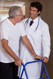 Doctor helping Patient use Walker. A doctor assisting a senior citizen onto his walker Royalty Free Stock Images