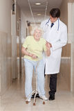 Doctor helping Patient use Walking Stick Stock Image
