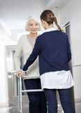 Doctor Helping Senior Patient With Walker In Rehabilitation Cent Stock Photography