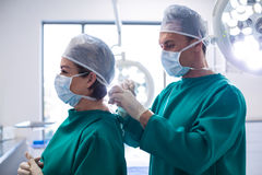 Doctor helping surgeon in tying surgical mask Royalty Free Stock Photos