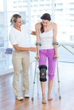 Doctor helping woman walking with crutches Royalty Free Stock Photography