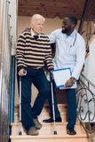 The doctor helps a man to go down the stairs in a nursing home. Stock Photography