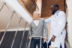 The doctor helps a man to go down the stairs in a nursing home. Royalty Free Stock Images