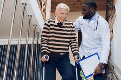 The doctor helps a man to go down the stairs in a nursing home. The doctor helps a men to go down the stairs in a nursing home. A men holds on to a walker for Stock Photo