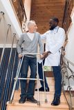 The doctor helps a man to go down the stairs in a nursing home. The doctor helps a men to go down the stairs in a nursing home. A men holds on to a walker for Stock Image