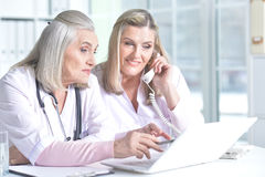 Doctor and her colleague using laptop Stock Image