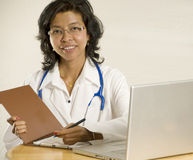 Doctor at her desk. Smiling and confident female Asian Doctor sitting down Royalty Free Stock Photos