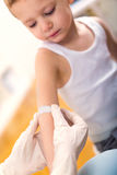Doctor in her practice putting a bandage on some hurt of a little boy Royalty Free Stock Photos