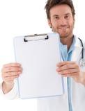 Doctor hermoso que celebra la sonrisa de la hoja en blanco Imagenes de archivo