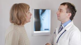 Doctor hermoso que habla con su paciente para el chequeo anual en el hospital Sonrisa de la mujer metrajes