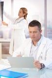 Doctor hermoso que trabaja en oficina Foto de archivo