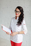 Doctor hermoso sonriente de la mujer en uniformes blanco-y-rojos con imágenes de archivo libres de regalías