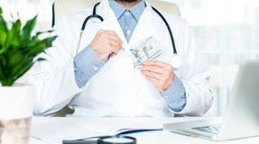 Doctor hiding hundred dollar bill. Accepting bribe Royalty Free Stock Images