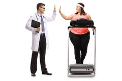 Doctor high-fiving an overweight woman exercising on a treadmill Royalty Free Stock Image