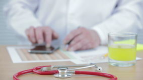 Doctor at his desk typing on his smart phone. With a red stethoscope and a glass of orange juice in front of him stock video footage