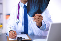 Doctor at his desk working with medical equipment in the background Royalty Free Stock Image
