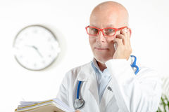 A doctor in his office with phone Stock Images