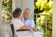 Doctor with his patient in her wheelchair. Senior doctor with his patient in her wheelchair Stock Photography