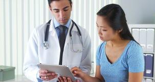 Doctor hispánico que habla con el paciente con resultados de la prueba en la tableta Fotografía de archivo libre de regalías