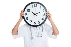 Doctor hold a clock over her face Stock Photos