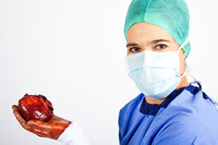 Doctor hold heart in blue with mask Stock Photos