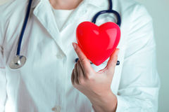 Doctor hold heart. Female doctor holding red heart Stock Image