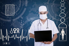 Doctor hold laptop on blue digital background Royalty Free Stock Photo