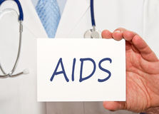 Doctor holding AIDS sign with text. In his hand royalty free stock image
